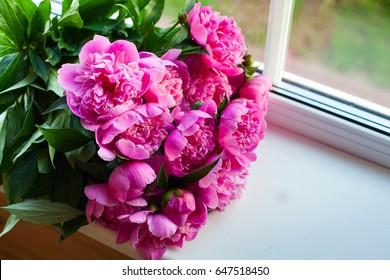 pink peonies on window-sill