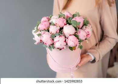 Pink peonies in pink round box. Beautiful peony flower in womans hands for catalog or online store. Floral shop concept. Flowers delivery. copy space