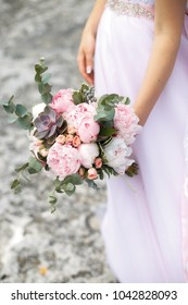 Pink peonies wedding bouquet in bride's hands