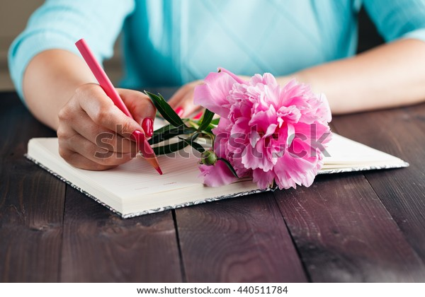 Pink peonies in woman hands on aged wooden table