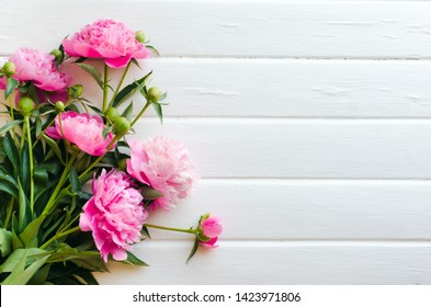 Pink peony flowers on white wooden table. womans day or wedding background.