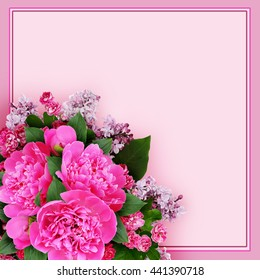 Pink peony, hawthorn and lilac flowers bouquet in a corner on pink background