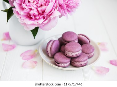 Pink peony with macarons on a white wooden table