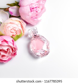 Pink perfume bottle with flowers on light background. Perfumery, cosmetics, fragrance collection. Free space for text.