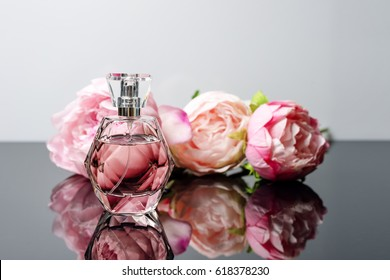 Pink perfume bottle with flowers on black and white background. Perfumery, cosmetics, fragrance collection