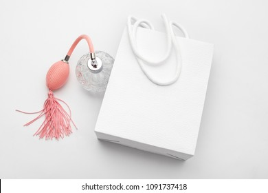 Pink perfume bottle with white paper shopping bag. Perfumery, cosmetics, fragrance collection. Sale, fashion, shopping and advertising theme.