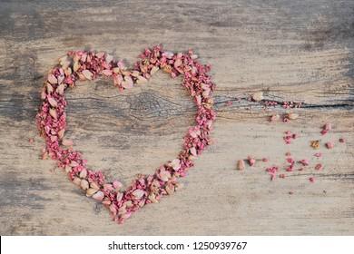 Pink petals shape heart on wood background, Mexican Creeper (Antigonon Leptopus) or Coral Bells, coral vine, Coralita, bee bush or San Miguelito vine.