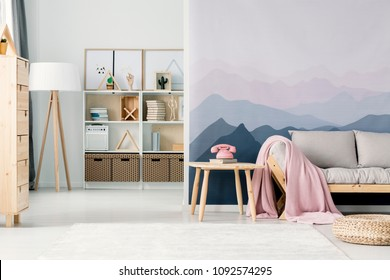 Pink phone on wooden table next to a beige sofa in living room interior with mountain wallpaper