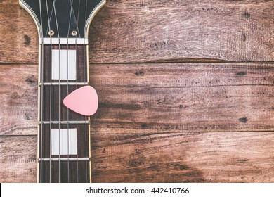 pink pick & electric guitar fretboard, on old wood + vintage filter for music background