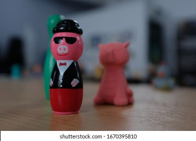 Pink Pig Figure with Sunglasses and Tuxedo Suit on Wooden Desk Table with collection of Kids Toys, Green Skittle, Red Tiger Eraser, Close Up
