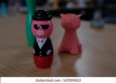 Pink Pig Figure with Sunglasses and Tuxedo Suit on Wooden Desk Table with collection of Kids Toys, Green Skittle, Red Tiger Eraser, Macro Close Up, Blurred Background