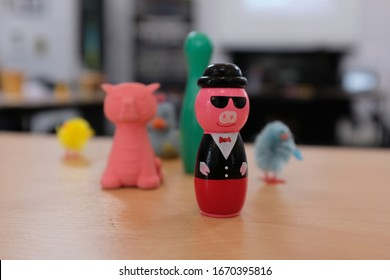 Pink Pig Figure with Sunglasses and Tuxedo Suit on Wooden Desk Table with collection of Kids Toys, Green Skittle, Red Tiger Eraser, Fluffy Chicks, Close Up