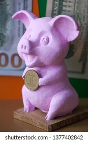 Pink Pig holding hryvna coin. Pig with hryvna coin against the background US dollars background. Ukrainian economy, Business, benefit.