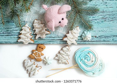 Pink pig, symbol of 2019. Happy New Year. Crochet toy for child. On table threads, needles, hook, cotton yarn. Handmade crafts on holiday with your own hands. Gingerbread and meringue. Christmas card
