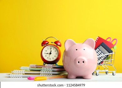 Pink piggy bank with alarm clock and school supplies on yellow background