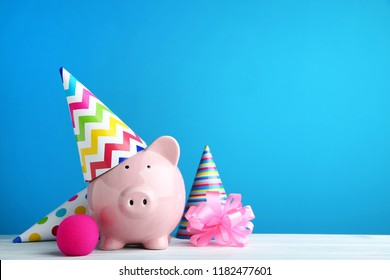 Pink piggy bank with birthday cap on blue background