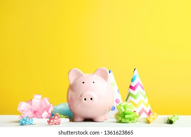Pink piggy bank with birthday cap and blowers on yellow background