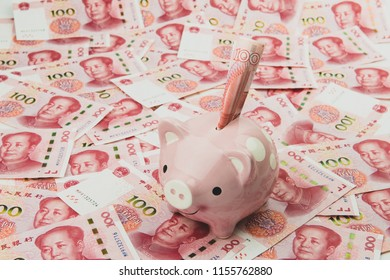 Pink piggy bank and Chinese dollar currency notes.. Chinese currency as background.
