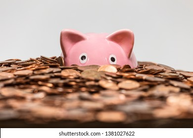 Pink piggy bank drowning in ocean of copper pennies.