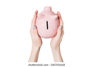 Pink piggy bank in female hands isolate on white background. View from above.