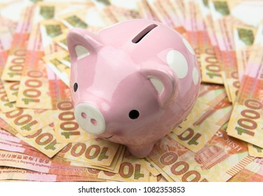 Pink piggy bank and Hong Kong dollar currency notes.