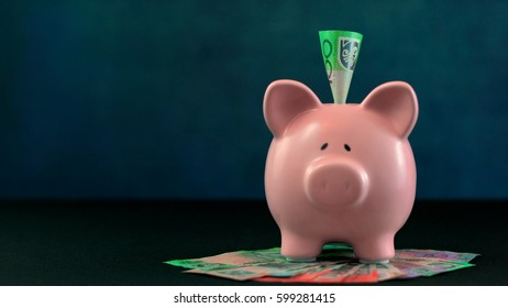 Pink Piggy bank money concept on dark blue background with Australian cash and a one hundred dollar note inserted.