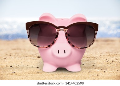 Pink piggy bank on beach