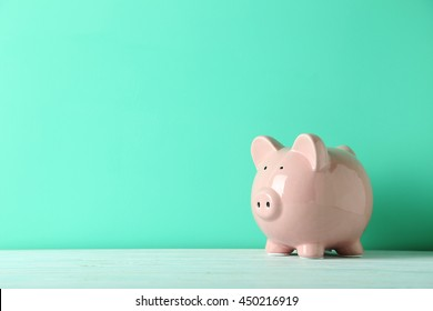 Pink piggy bank on a green wooden table