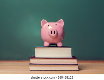 Pink Piggy bank on top of books with chalkboard in the background as concept image of the costs of education