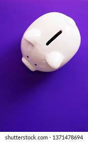 Pink piggy bank on violet background. Soft focus. Top view.