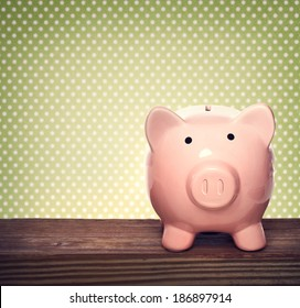 Pink piggy bank over green polka dots background