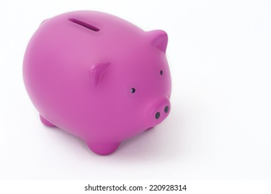 A pink piggy bank photographed on a textured white background.