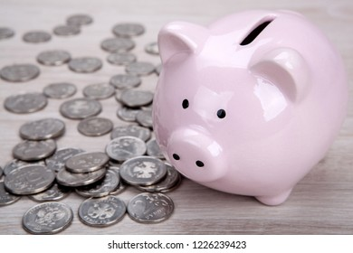 pink piggy bank with Russian ruble coins close up