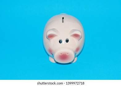 Pink piggy Bank in the shape of a pig is on the right blue background. On the left there is a place under the inscription. Piggy bank with copy space on blue background