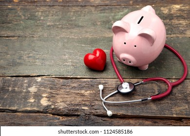 Pink piggy bank with stethoscope and red heart on wooden table