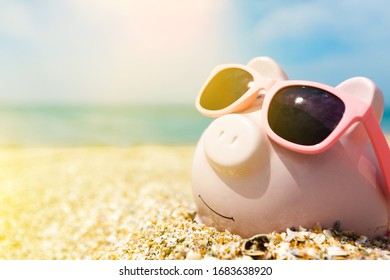Pink piggy bank with sunglasses on the beach