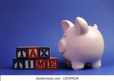 Pink piggy bank with Tax Time message on building blocks for Tax Day or End of Financial Year financial returns or retail stock-take sales.