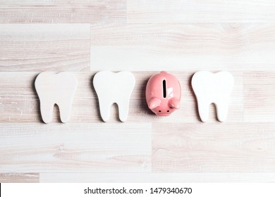 Pink piggy bank with teeth on a light wooden background. Investing in dental health care.