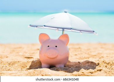 Pink Piggy Bank Under The Small Parasol During Summer At Beach