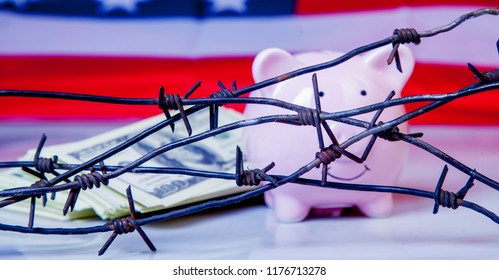 Pink piggy bank and US Dollar money wrapped in barbed wire against United States national flag as symbol of economic warfare, sanctions and embargo busting