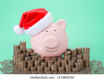 Pink piggy bank wearing a Santa hat smiling facing viewer surrounded by stacks of coins, green background.