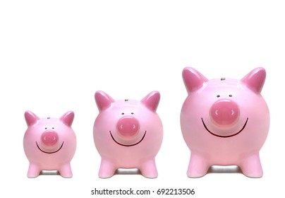 Pink piggy banks in three different sizes / Saving money concept for growth concept