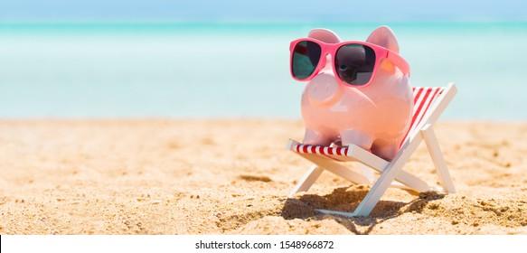 Pink Piggybank Wearing Eyeglasses On Deck Chair Over The Sandy Beach