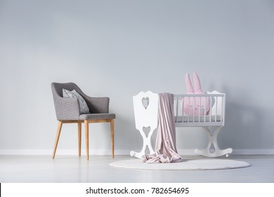 Pink pillow and blanket in white cradle next to a grey chair in simple baby's bedroom interior with copy space