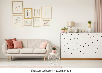 Pink pillow on beige sofa in feminine living room interior with plant and gallery of posters