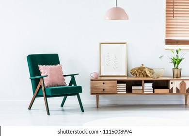 Pink pillow on green armchair next to a rustic cupboard in living room interior with poster