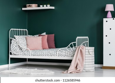 Pink pillow on white bed in green girl's room interior with lamp on cabinet