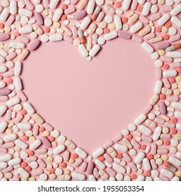 Pink pills arranged in a heart shape on pink background. Creative medicine, drugstore, healthcare and pharmacy concept. Frame border with copy space. Flat lay, top view.