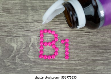Pink pills forming shape to B1 alphabet on wood background
