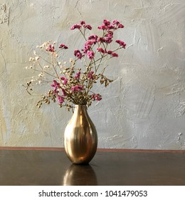 Pink pity dry flower in golden vase with vintage wall